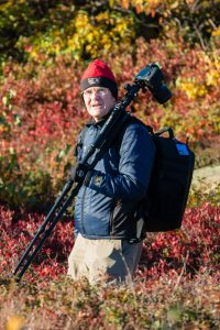 man carrying folded tripod with mounted camera on shoulder and backpack walking through Fall colored brush